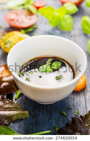 salad vinegar in white  bowl with basil leaves, close up - stock photo