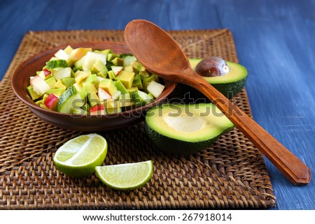 Salad with apple and avocado in bowl on wicker stand close up - stock photo