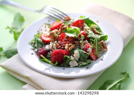 Salad with arugula, strawberries, goat cheese and walnuts dressed with balsamic vinegar and olive oil - stock photo