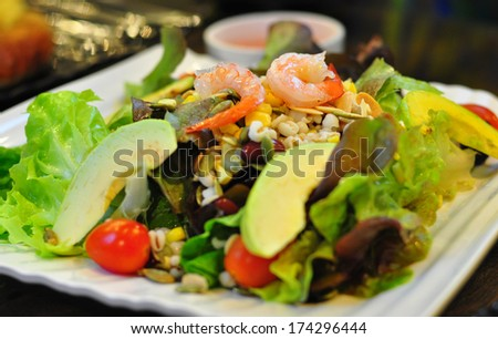 Salad with avocado and shrimp on a white dish. - stock photo