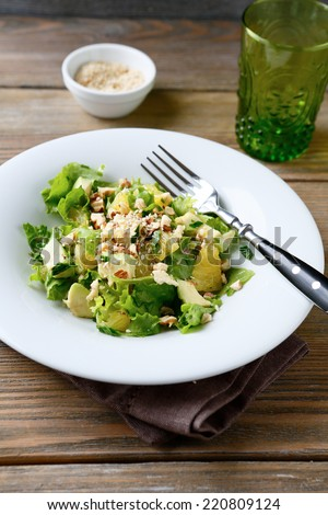 Salad with Avocado, Lettuce, Orange and Nuts on a bowl, delicious food - stock photo