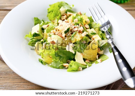 Salad with Avocado, Lettuce, Orange and Nuts on a white bowl, food close up