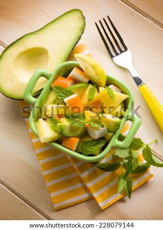 salad with avocado surimi and pineapple - stock photo