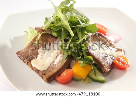 Salad with beef tongue and sauce on plate