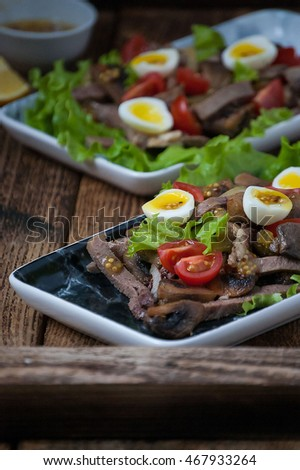 Salad with beef tongue, mushrooms, tomatoes, quail eggs and mustard dressing.