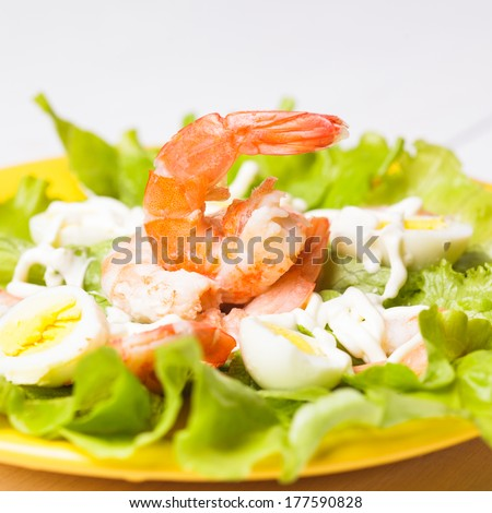 Salad with boiled shrimps, quail eggs and sauce - stock photo
