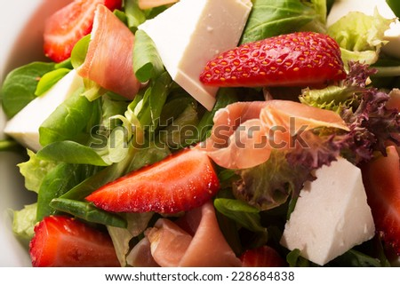 Salad with cheese, bacon, greens and strawberries - stock photo