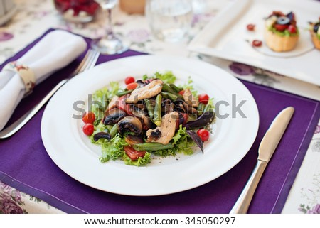 Salad with chicken and tomatoes in white plate on the table