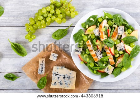 salad with chicken breast, spinach, celery, grapes and blue cheese Gorgonzola on a white dish, view from above - stock photo