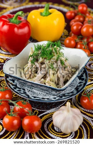 Salad with chicken fillet, mushrooms, beef tongue, cucumbers - stock photo