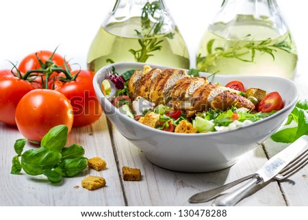 Salad with chicken, tomato, olive and fresh herbs - stock photo