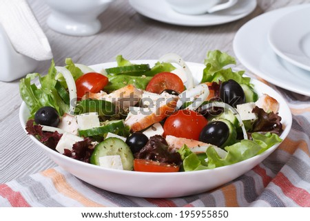 Salad with chicken, tomatoes, cucumbers, onions and cheese on the table.  - stock photo