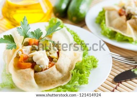 Salad with cooked vegetables, mayo and greens wrapped in a pancakes on a plate. Salad with cooked vegetables, mayo and greens wrapped in a pancake on a plate. Bottle oil and cucumber in the background - stock photo