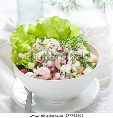Salad with cottage cheese, radish, cucumber and shrimps, selective focus