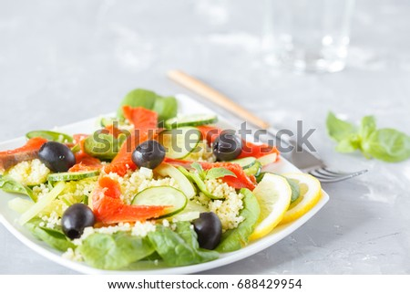 Salad with couscous, salmon, spinach and olives.