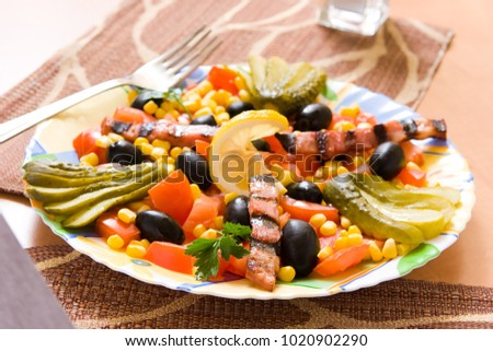 salad with cucumber, tomato, olives, meal and corn