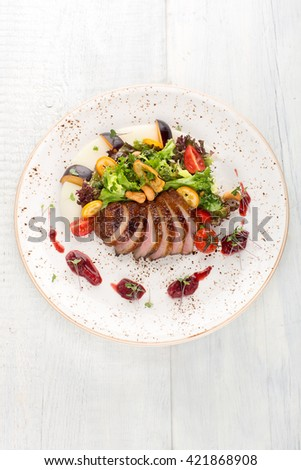 Salad with duck, melon, cashew nuts, tomatoes, jam on a white wooden background, top view