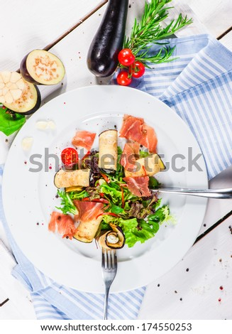 Salad with eggplant rolls, cheese, bacon and lettuce leaves