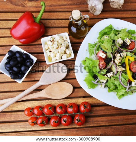 salad with feta cheese and fresh vegetables on wooden background - stock photo