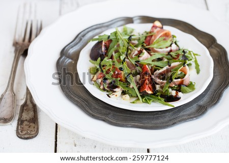 Salad with figs ,prosciutto , arugula and Parmesan cheese seasoned with balsamic sauce.selective focus - stock photo