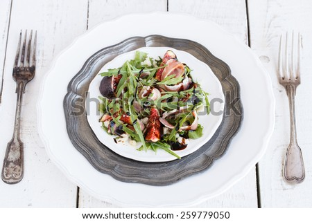 Salad with figs ,prosciutto , arugula and Parmesan cheese seasoned with balsamic sauce..selective focus - stock photo