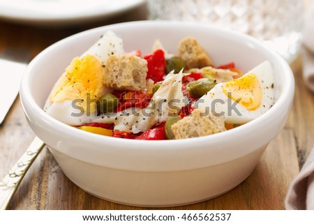 salad with fish and egg in white bowl
