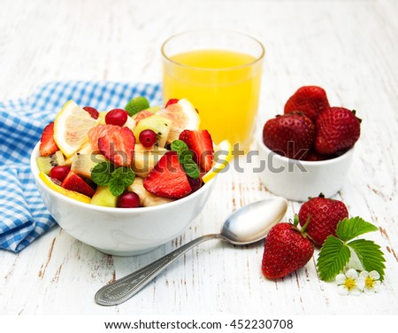 Salad with fresh fruits on a old wooden background