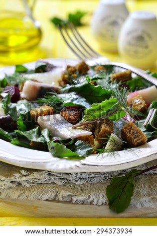 Salad with fresh organic beetroot,herrings and rye croutons on yellow wooden table.