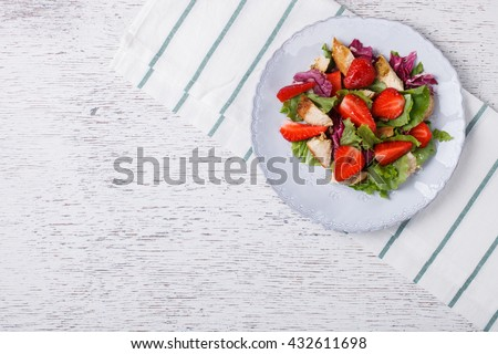 Salad with fresh strawberries,herbs and chicken meat,tossed with vinaigrette. Healthy food or diet concept.Copy space.selective focus. - stock photo