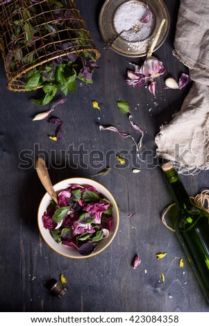 Salad with fresh summer greens and herbs on rustic wooden table. View from above, free text space. - stock photo