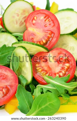 Salad with fresh tomatoes, cucumbers, bell peppers and rucola, close up view