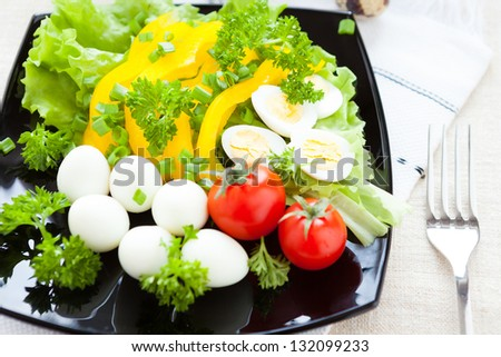 salad with fresh vegetables and quail eggs, closeup
