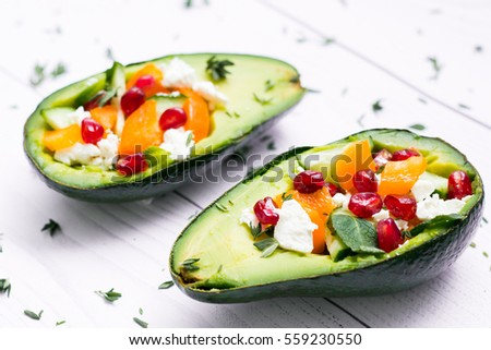 salad with fresh vegetables, feta cheese, avocado, garnets and tangerines. healthy diet or vegetarian food on a white background