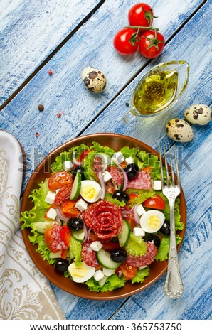 Salad with fresh vegetables, feta cheese, quail eggs, olives and salami. Plate with salad on a blue wooden background. Top view