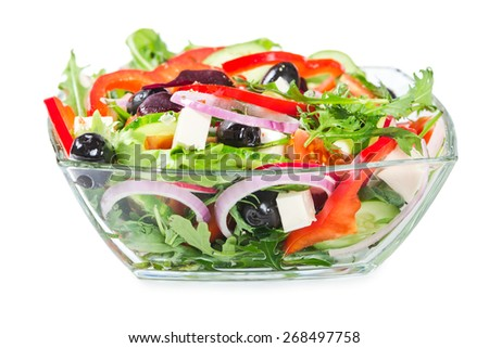 Salad with fresh vegetables, olives and cheese in a glass bowl isolated on white background - stock photo