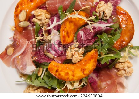 Salad with fried potato, cabbage, ham and nuts - stock photo