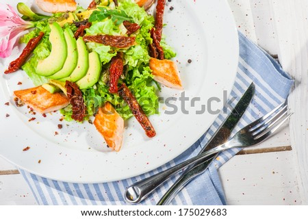 Salad with fried salmon, avocado and smoked tomatoes