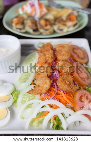 Salad with fried shrimp and cream
