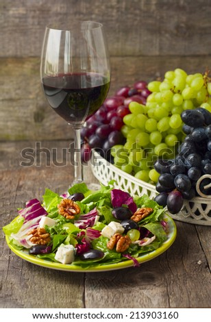 salad with grapes, herbs, walnuts and blue cheese and a glass of wine on wooden background