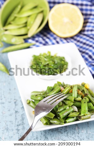 Salad with green beans and corn on plate, on color wooden background