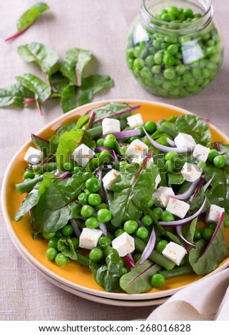 Salad with green peas, beans, red onion and feta cheese on textile background