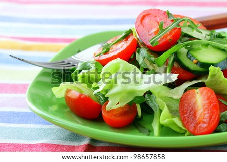 salad with lettuce and cucumber, arugula and cherry tomatoes - stock photo