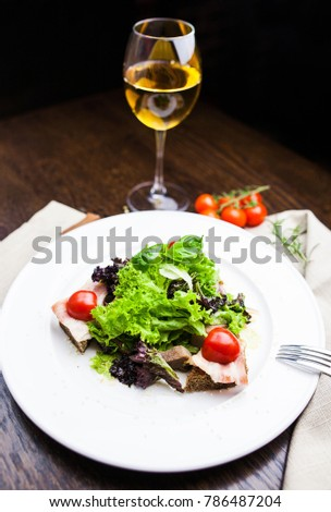 salad with lettuce, bacon and cherry tomatoes with glass of wine on a white plate