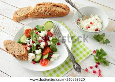 Salad with lettuce, tomato, pomegranate and white cheese - stock photo