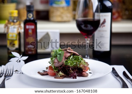 Salad with meat and basil on the plate