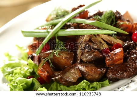 salad with meat and berries on the white dish - stock photo