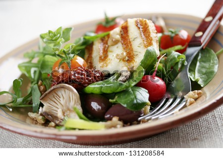 salad with mushrooms,spinach,tomatoes,sundried tomatoes,walnuts,haloumi cheese - stock photo