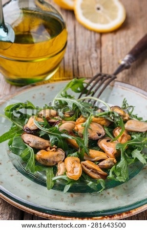 Salad with mussels and arugula on a glass plate with olive oil and lemon.selective focus - stock photo