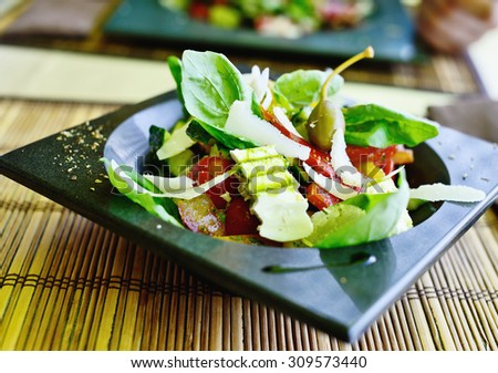 salad with parmesan cheese and other ingredients in soft selective focus - stock photo