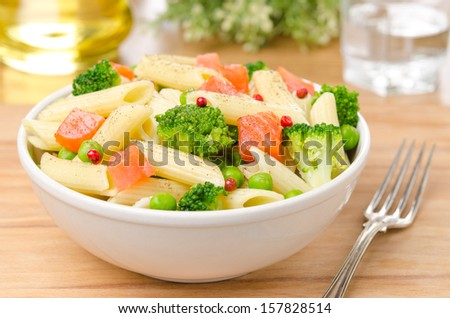 salad with pasta, smoked salmon, broccoli and green peas in a white bowl on a wooden table horizontal - stock photo